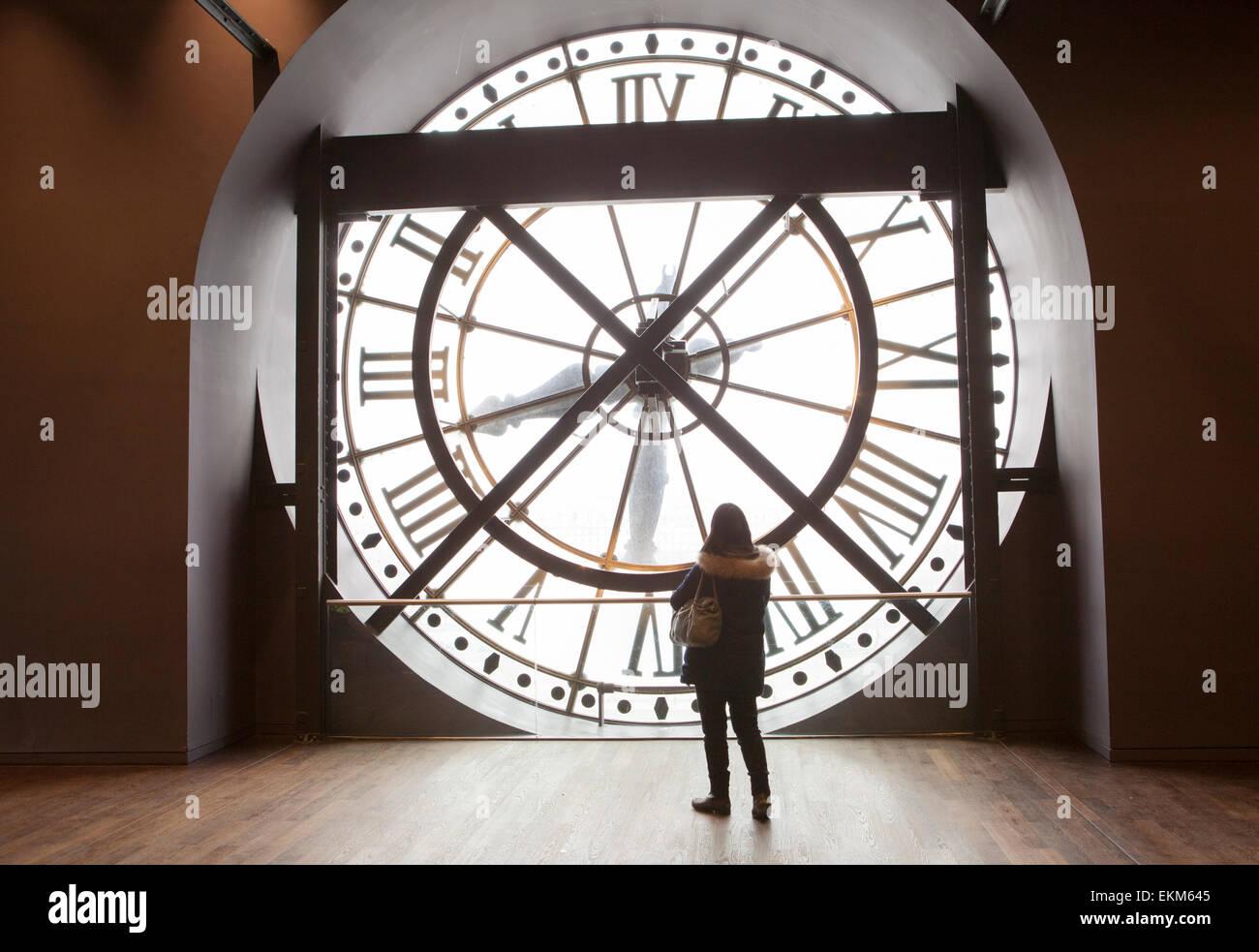 Eine Frau hinter der Stirnfläche eines Orsay Uhren im Pariser Musée d'Orsay Stockbild