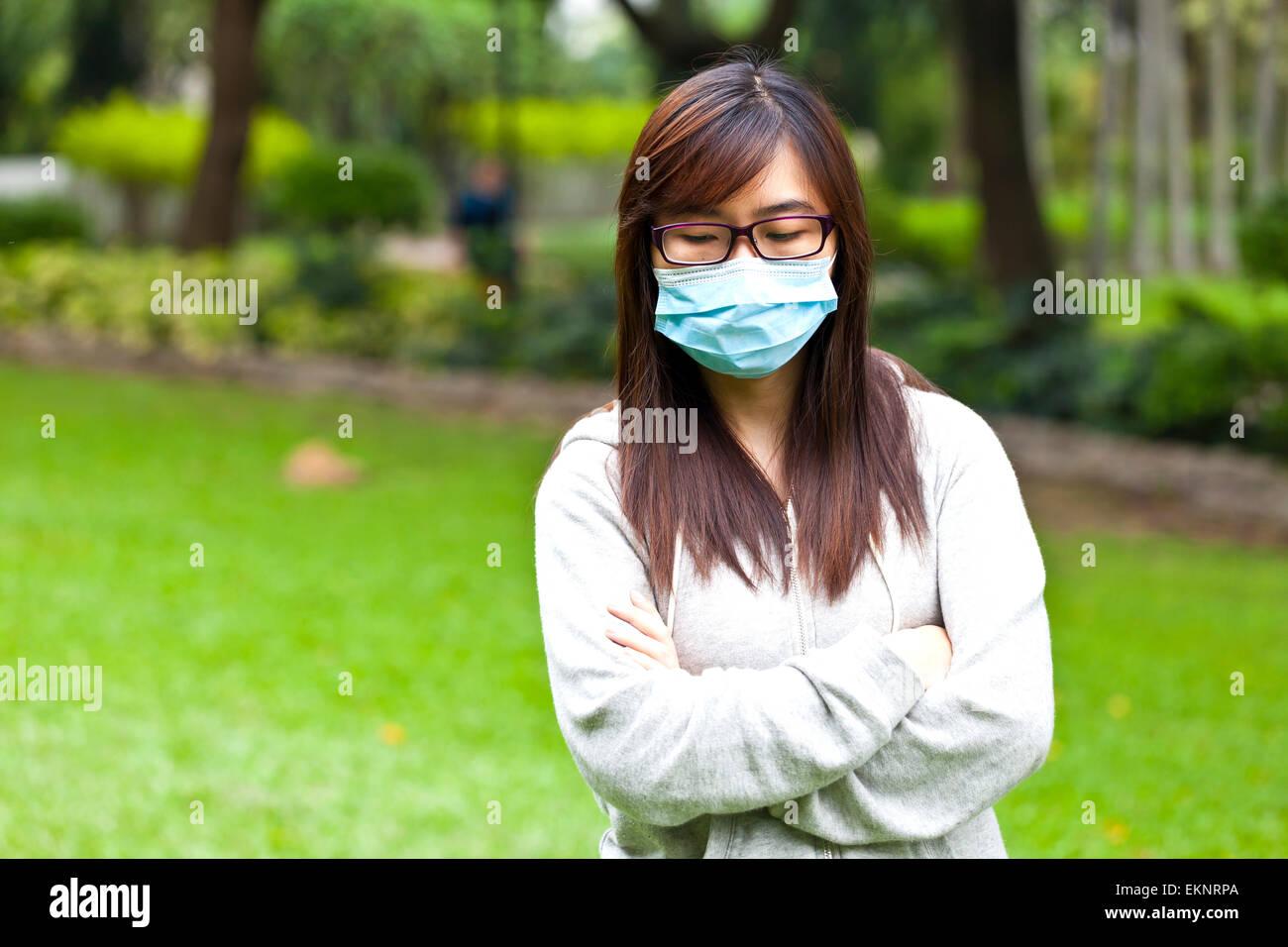 Frau trägt schützende Gesichtsmaske im park Stockfoto