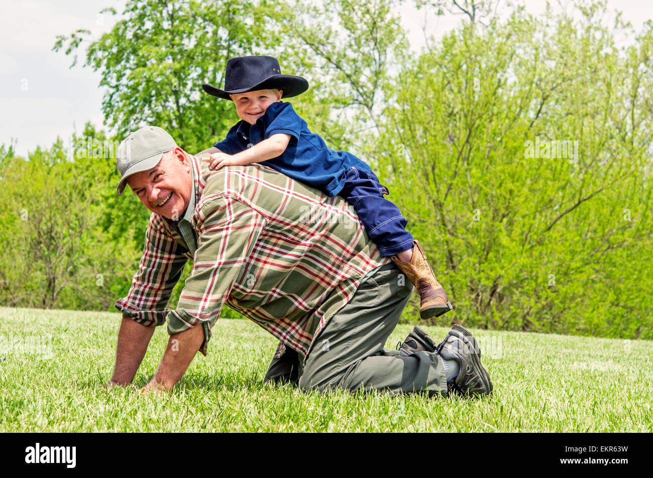 Junge spielt auf Großvaters zurück Stockbild