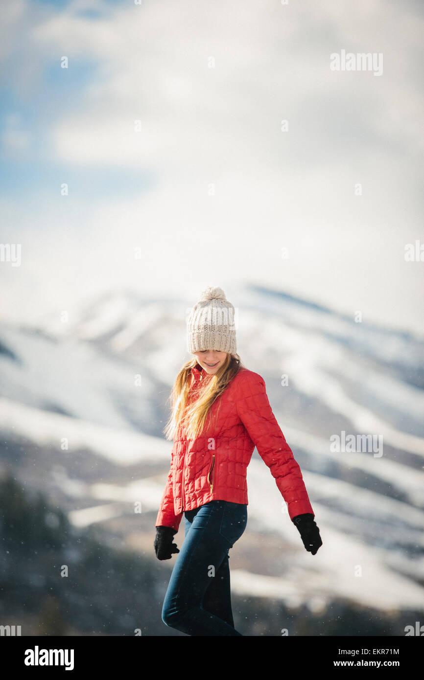 Ein junges Mädchen in einem roten Mantel und Wollmütze im Freien im Winter. Stockfoto