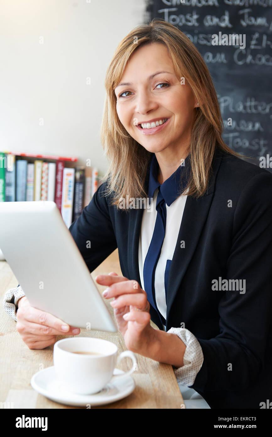 Geschäftsfrau mit Digital-Tablette In Cafe Stockbild
