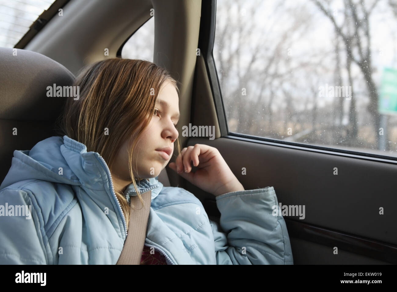 Ein Mädchen sitzt auf dem Rücksitz eines Autos schaut aus dem ...