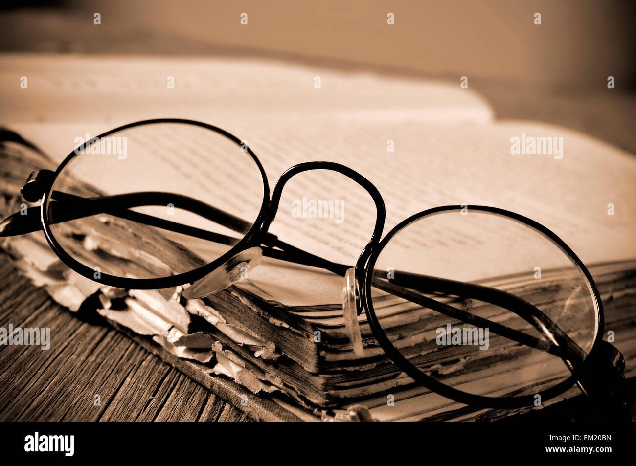 ein paar Runde-gerahmte Brille auf einem alten Buch, auf einem ...
