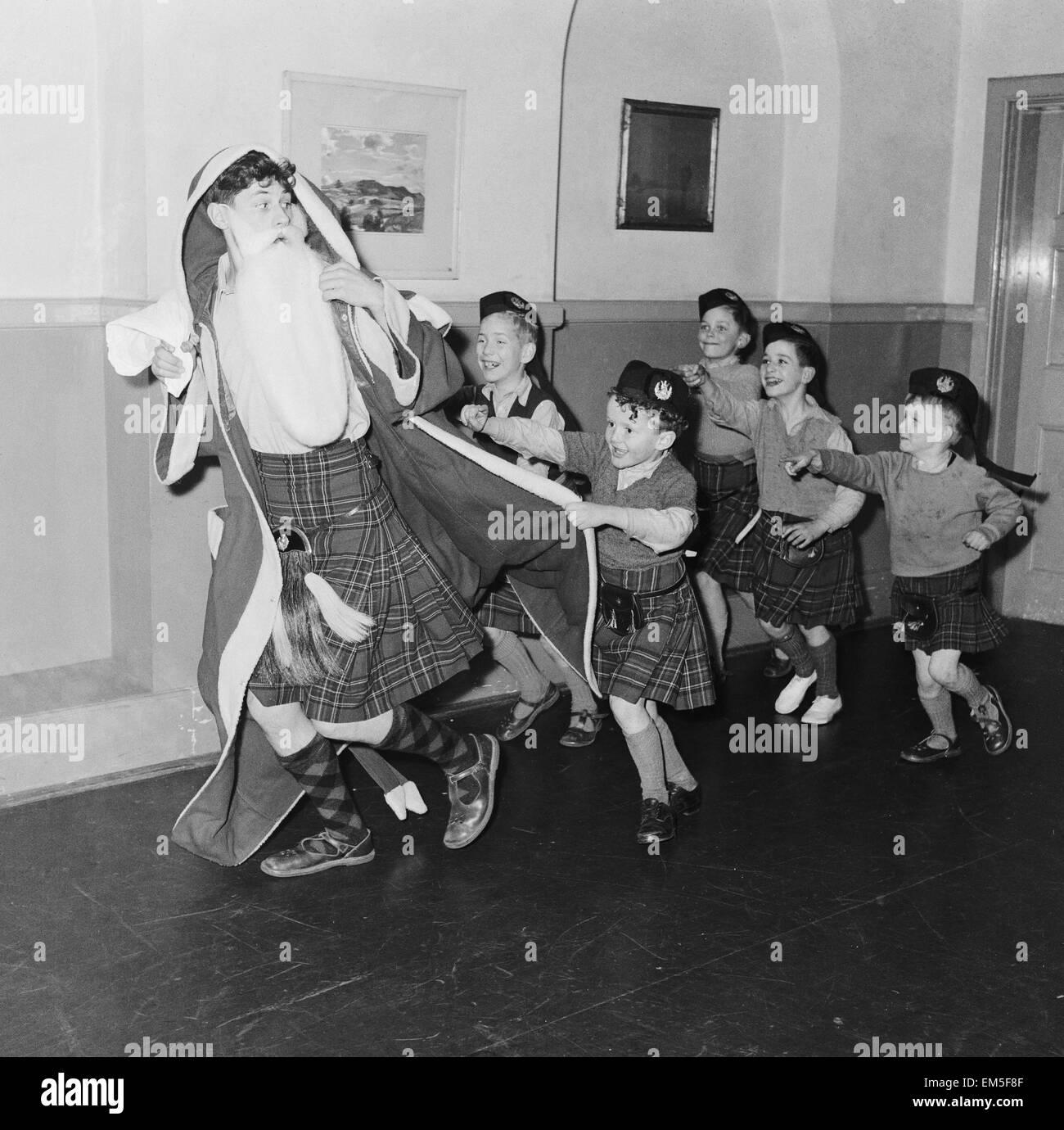 Kinder mit dem Weihnachtsmann auf ein Weihnachtsfest feiern. 22. Dezember 1957. Stockbild