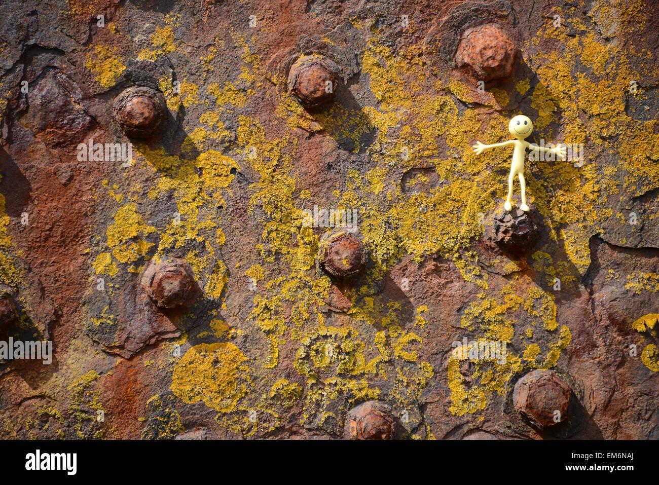 Gelber Smiley-Mann im Urlaub in den äußeren Hebriden - balanciert er hier auf einem rostigen niet eines Stockbild