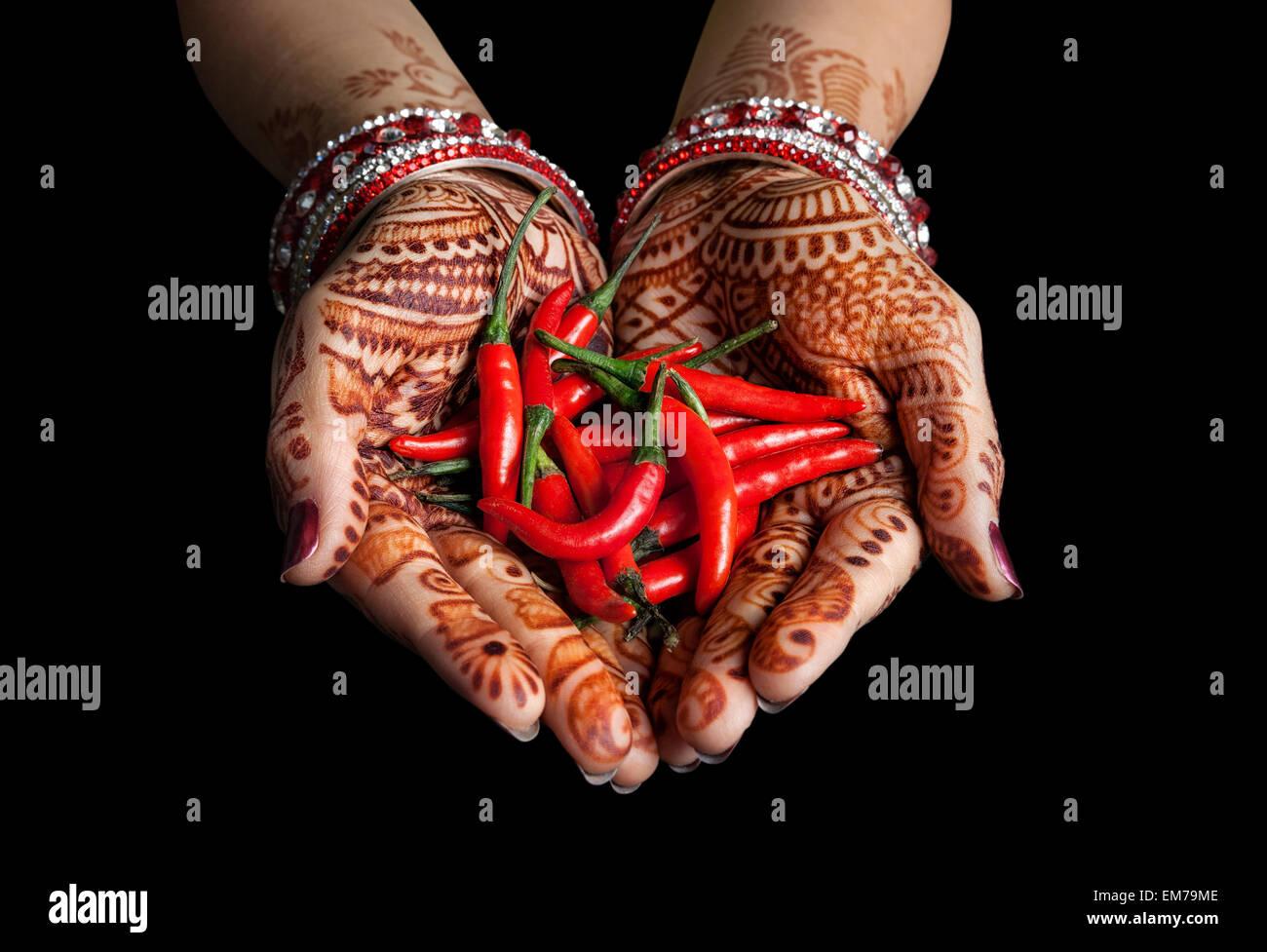 Frau Hände mit Henna roten Chili auf schwarzem Hintergrund mit Beschneidungspfad isoliert halten Stockbild