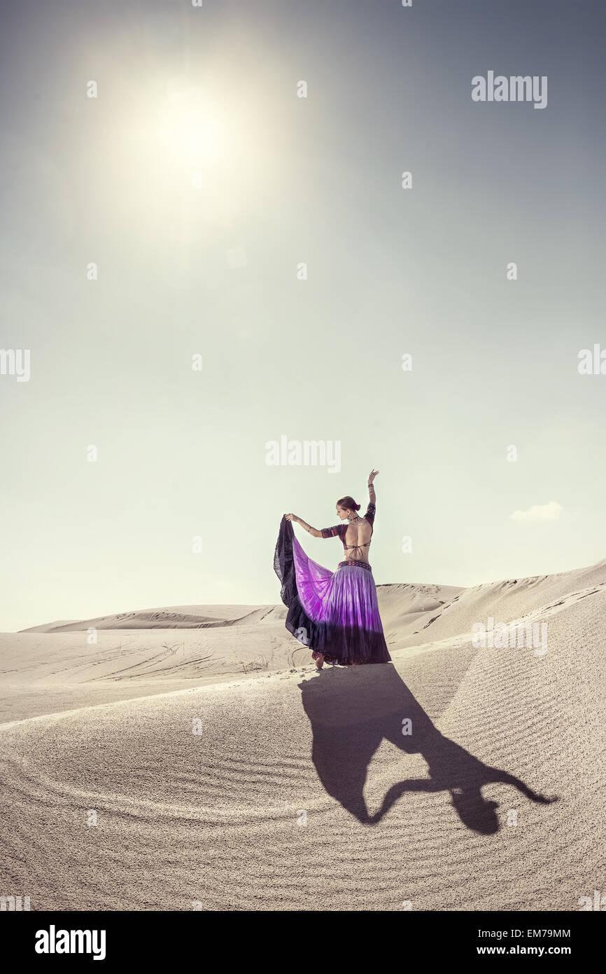 Frau in violetten Rock tanzen in der Wüste Stockbild
