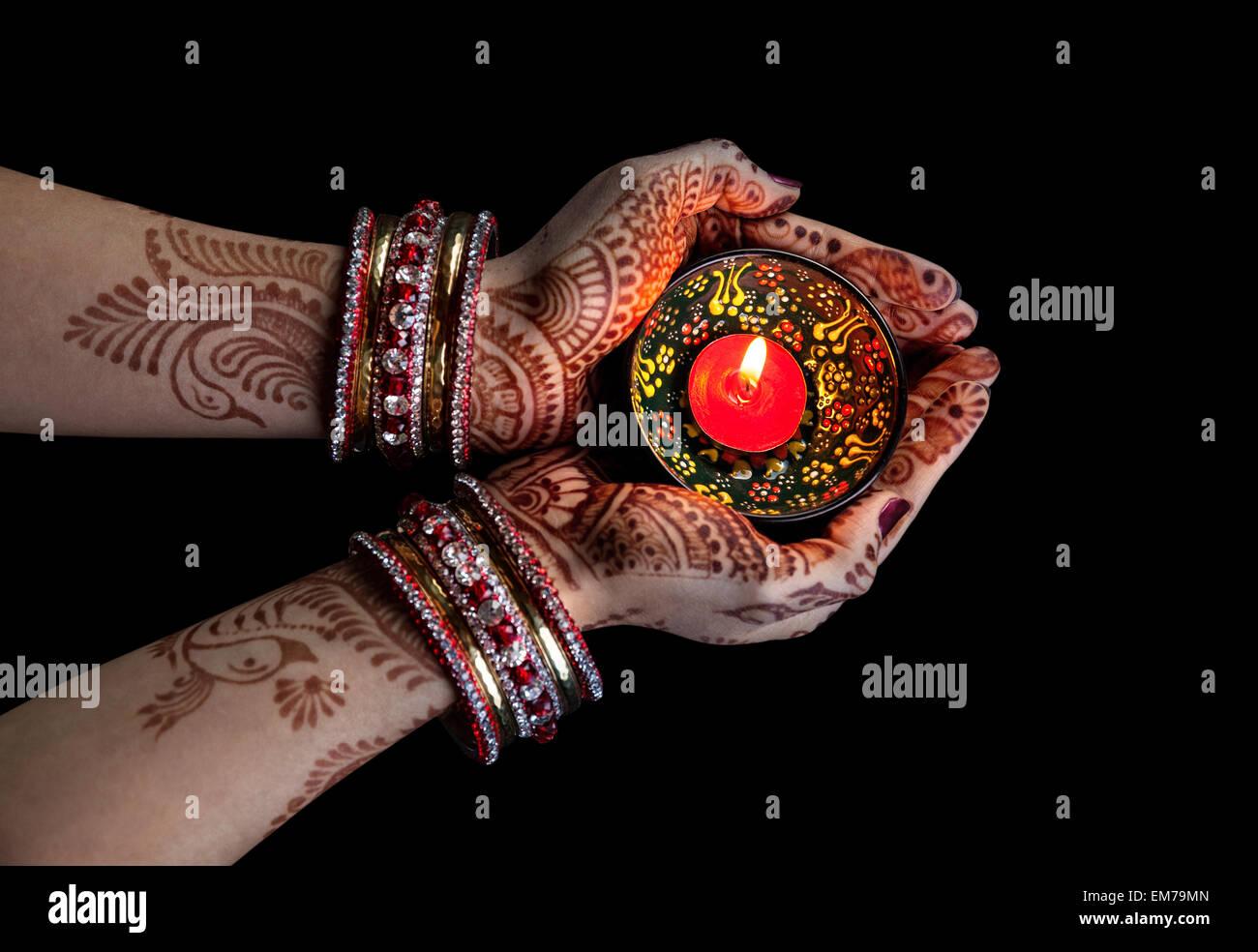 Frau Hände mit Henna mit Kerze auf Beschneidungspfad auf schwarzem Hintergrund isoliert Stockfoto