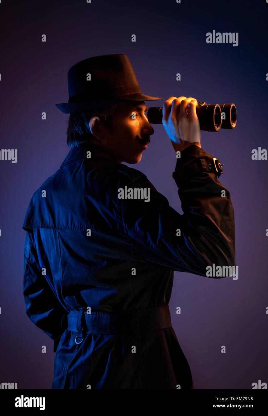 Mann im schwarzen Hut mit binokularen Spionage für jemanden auf dunklem Hintergrund Stockbild