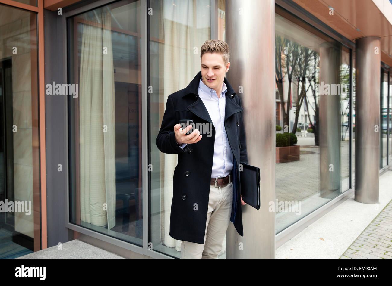 Geschäftsmann mit Smartphone durch den Bau Stockbild
