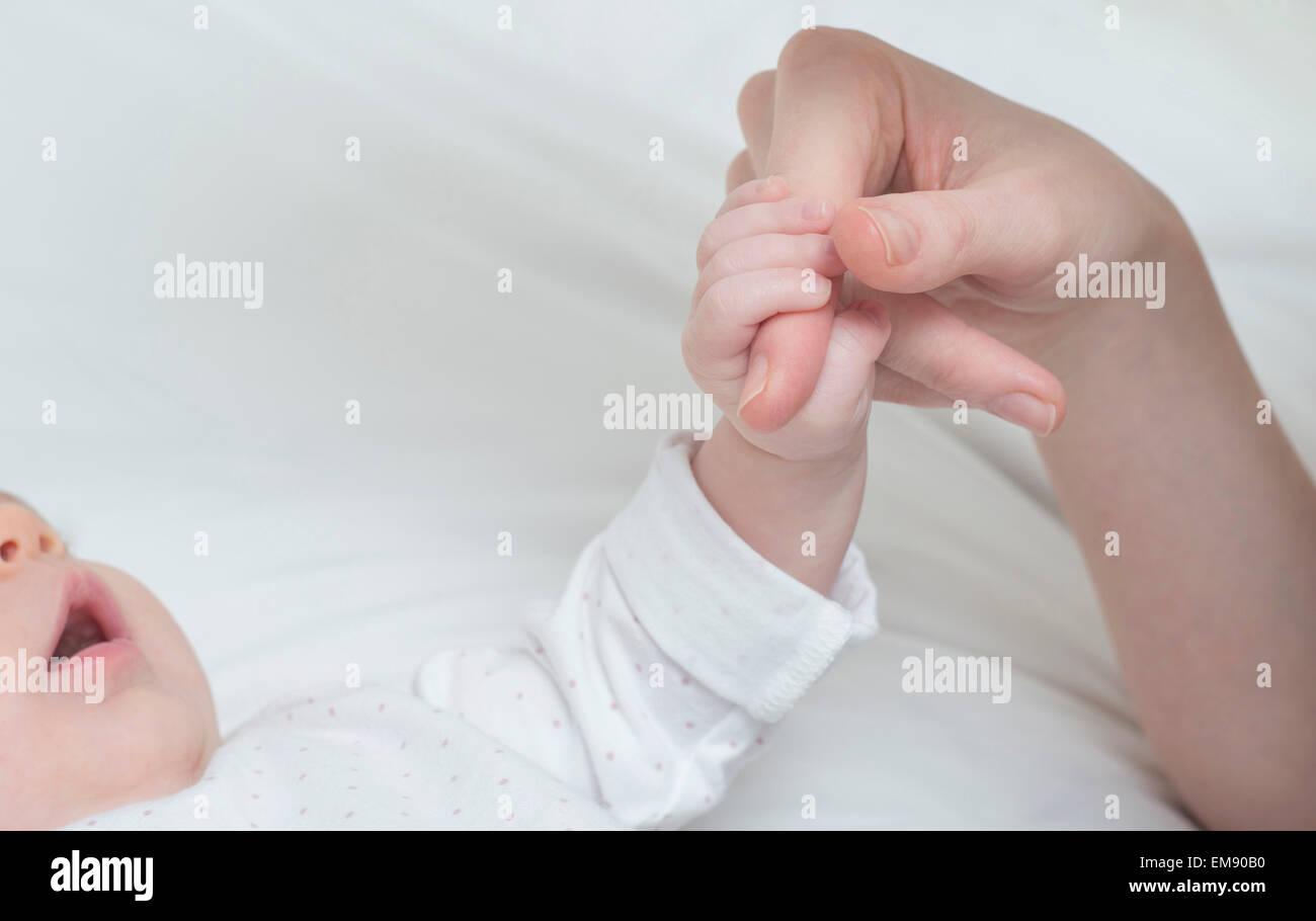 Baby Mädchen halten Mutter Finger auf Bett Stockbild