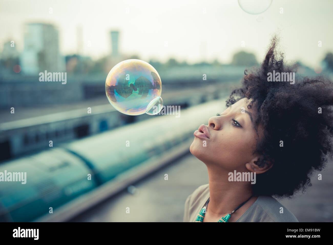 Junge Frau bläst Seifenblasen im Industriegebiet der Stadt Stockbild