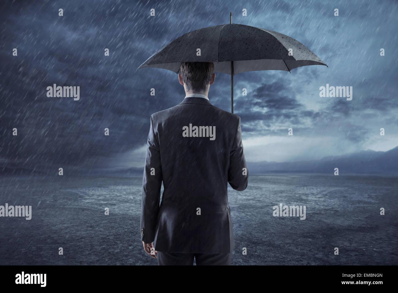 Deprimiert Geschäftsmann stehend mit einem Regenschirm Stockfoto