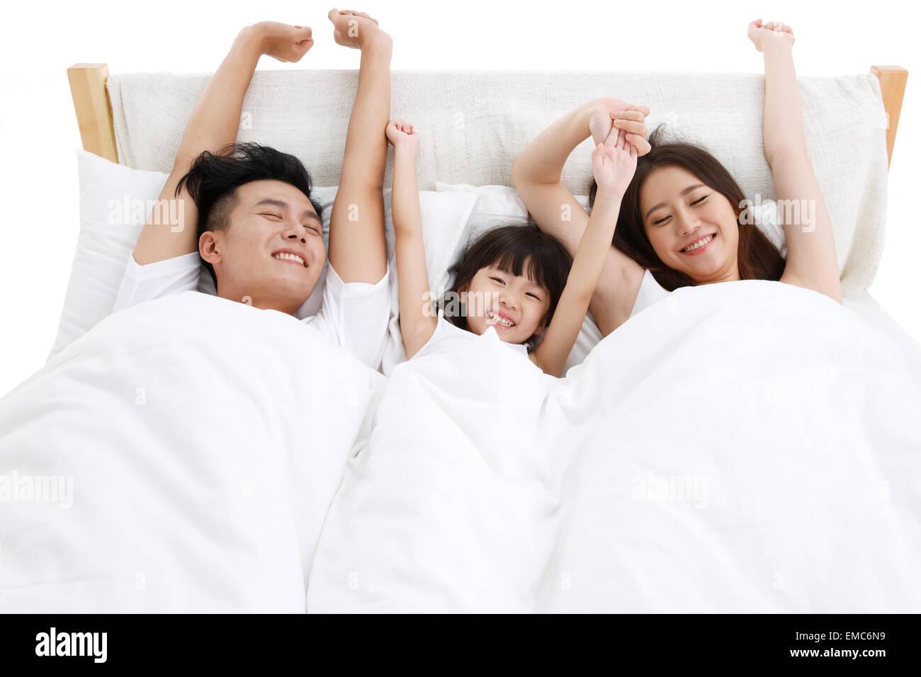 Das Glück einer Familie von drei in das Bett des Schlafzimmers aufgewacht Stockbild