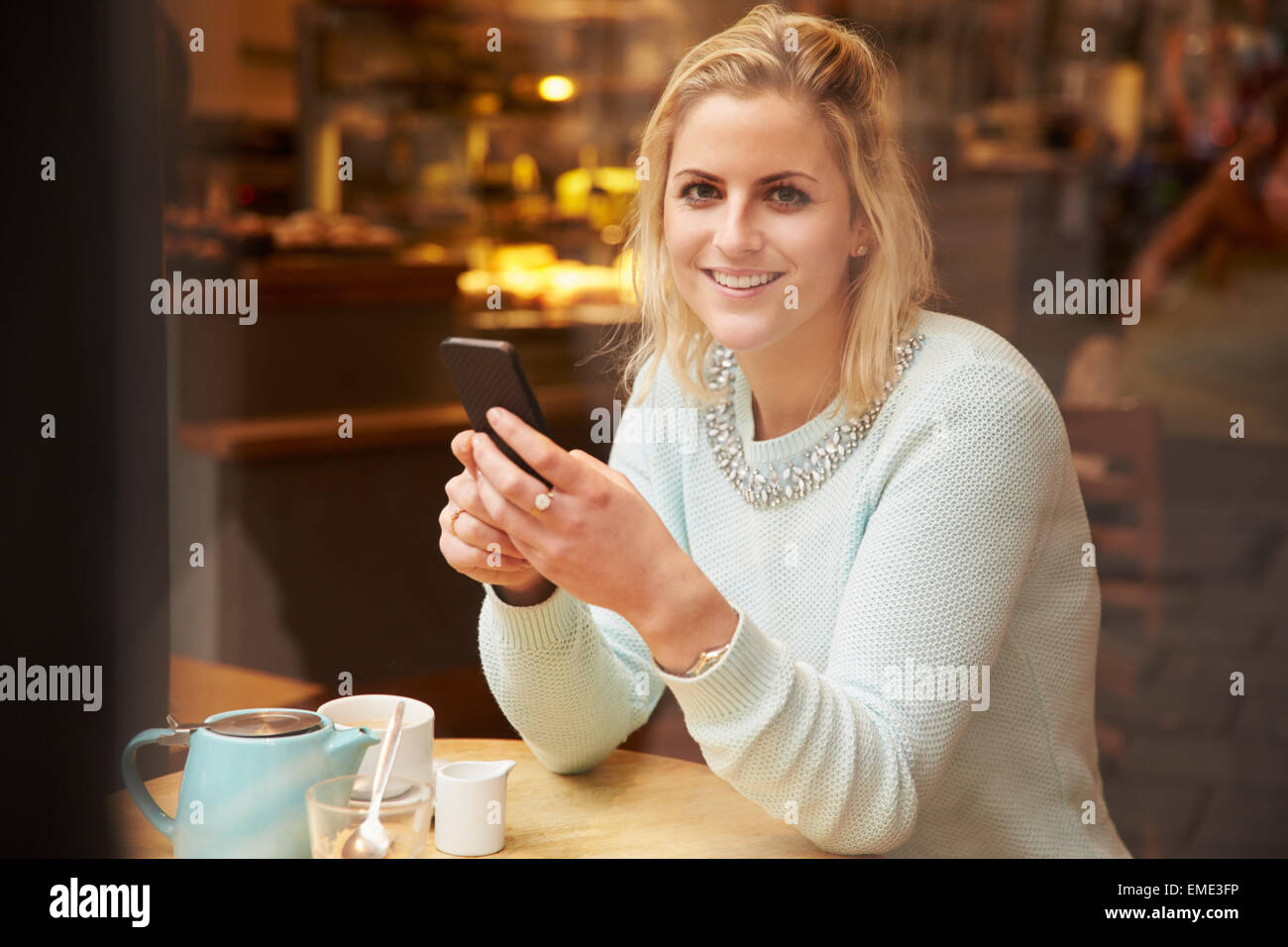 "Frau angesehen durch Fenster des Caf ""mit Mobiltelefon Stockbild"