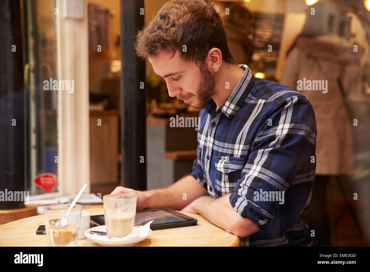 """Mann betrachtet durch Fenster des Caf """"mit Digital-Tablette Stockbild"""