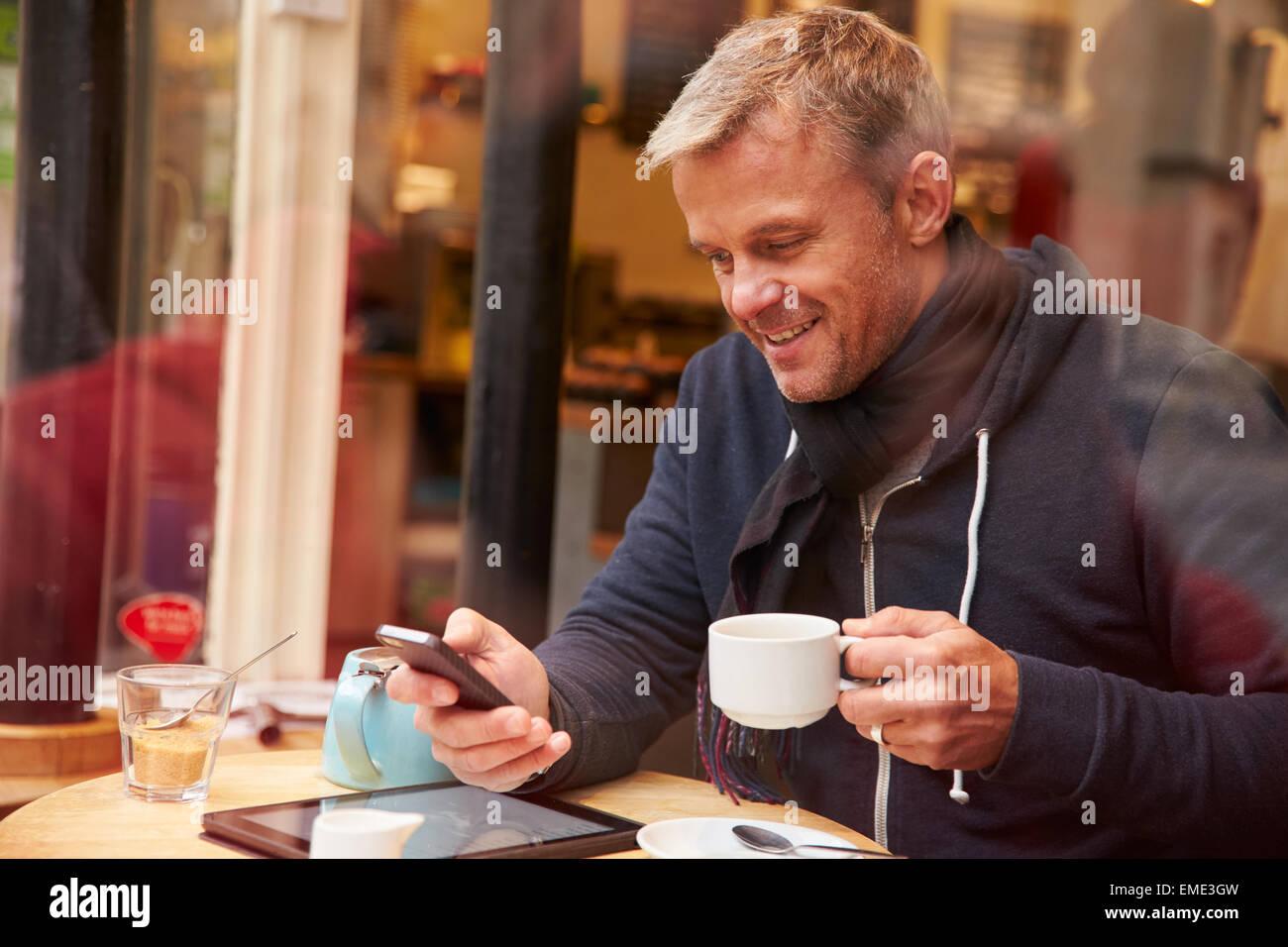 """Mann betrachtet durch Fenster des Caf """"mit Mobiltelefon Stockbild"""