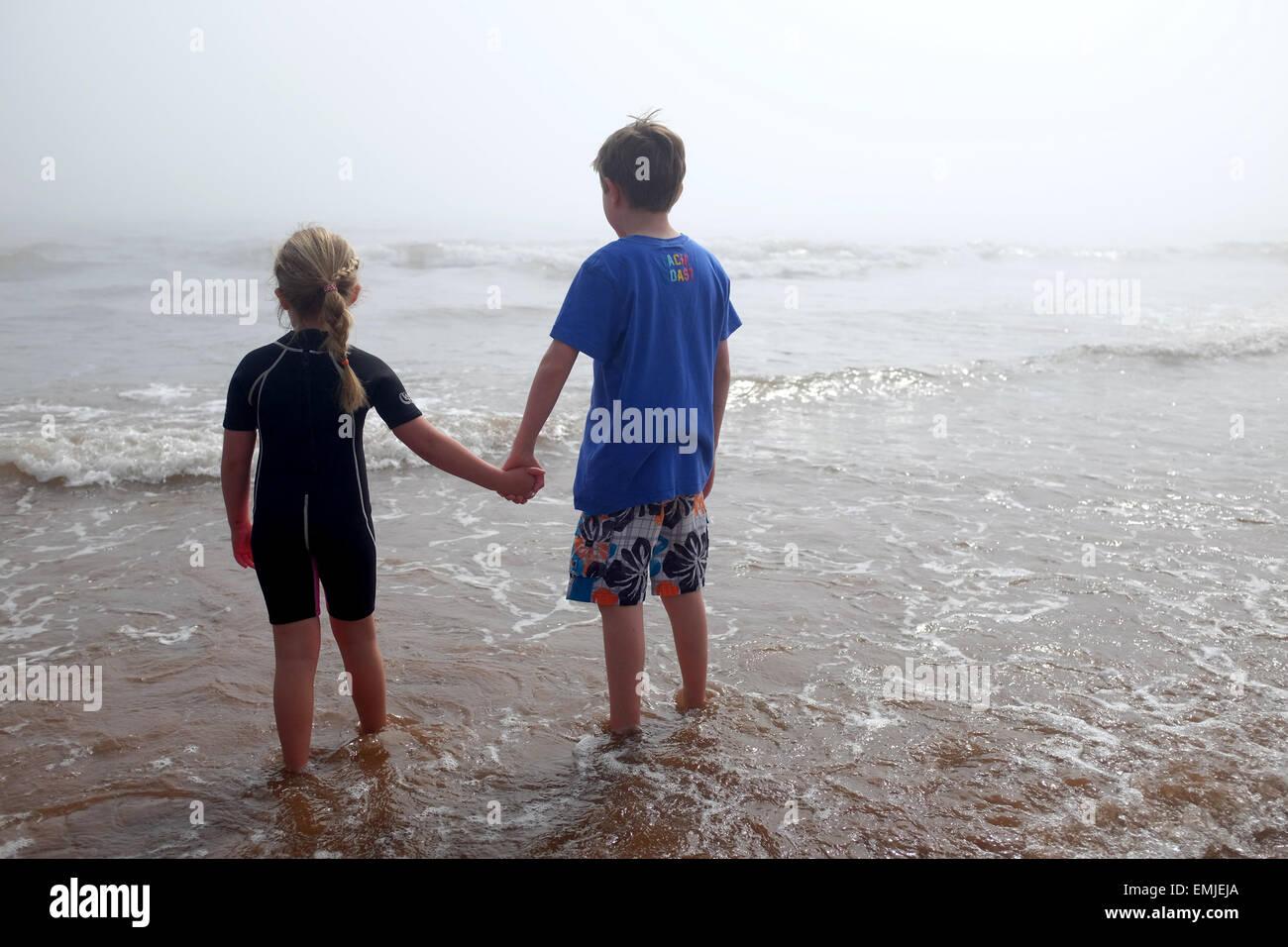 Ein kleiner Junge und ein Mädchen Hand in Hand Blick auf das Meer an einem nebligen Tag Stockbild