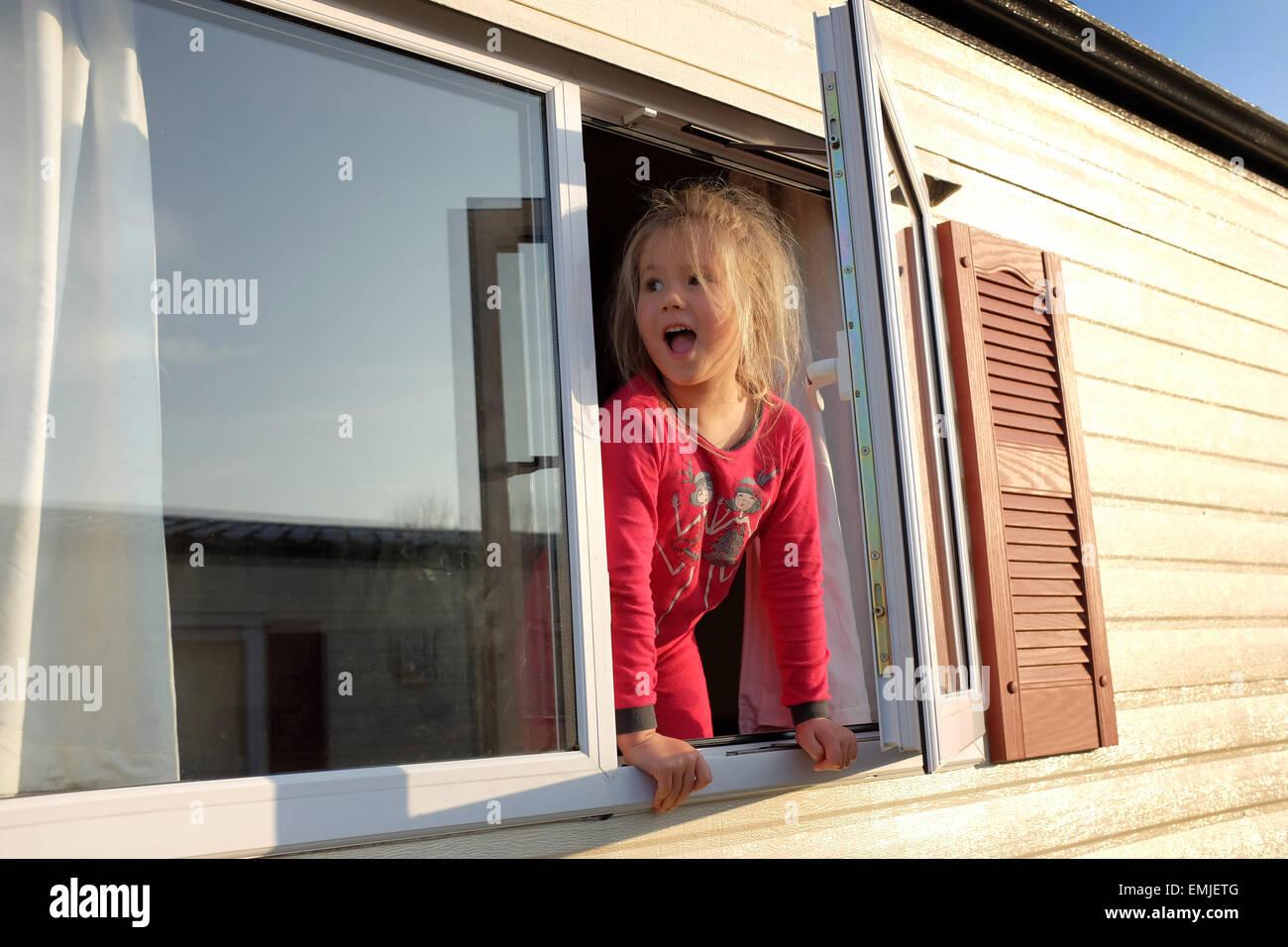 Ein junges Mädchen in ihrem Pyjama blickt aus dem Fenster einer Karawane zu Beginn eines neuen Tages Stockbild
