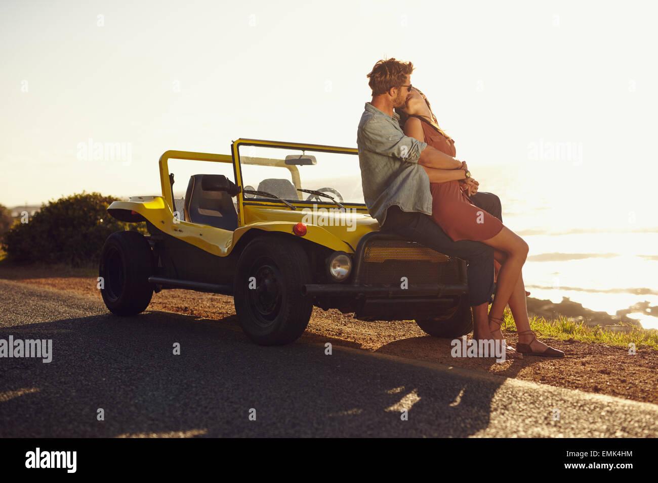 Romantische junges Paar auf Motorhaube ihres Autos sitzen und küssen. Junges Paar teilen einen leidenschaftlichen Stockbild