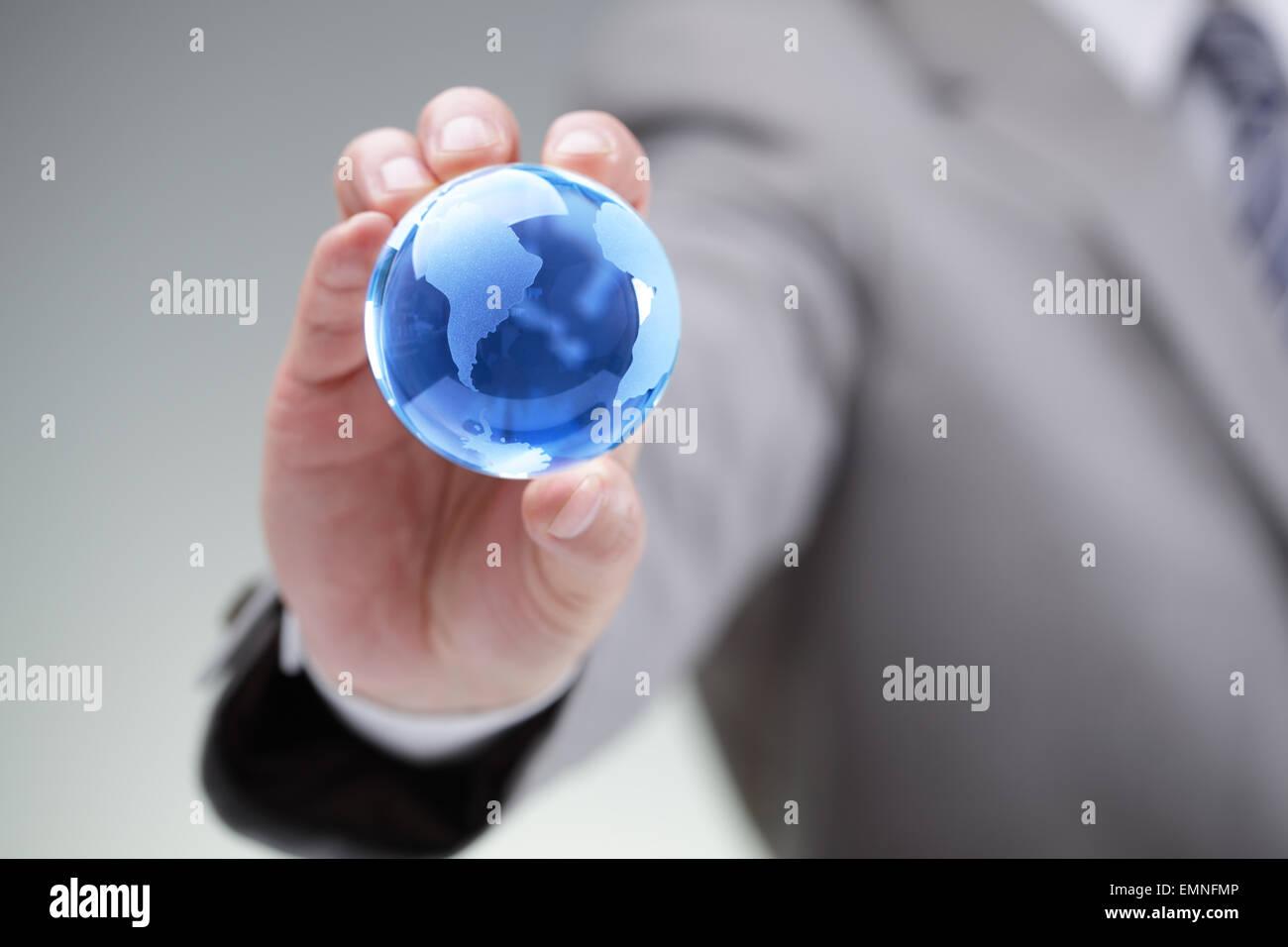 Business-Mann hält eine blaue Kugel in seiner Hand-Symbol für globale Unternehmen, Kommunikation oder Stockbild