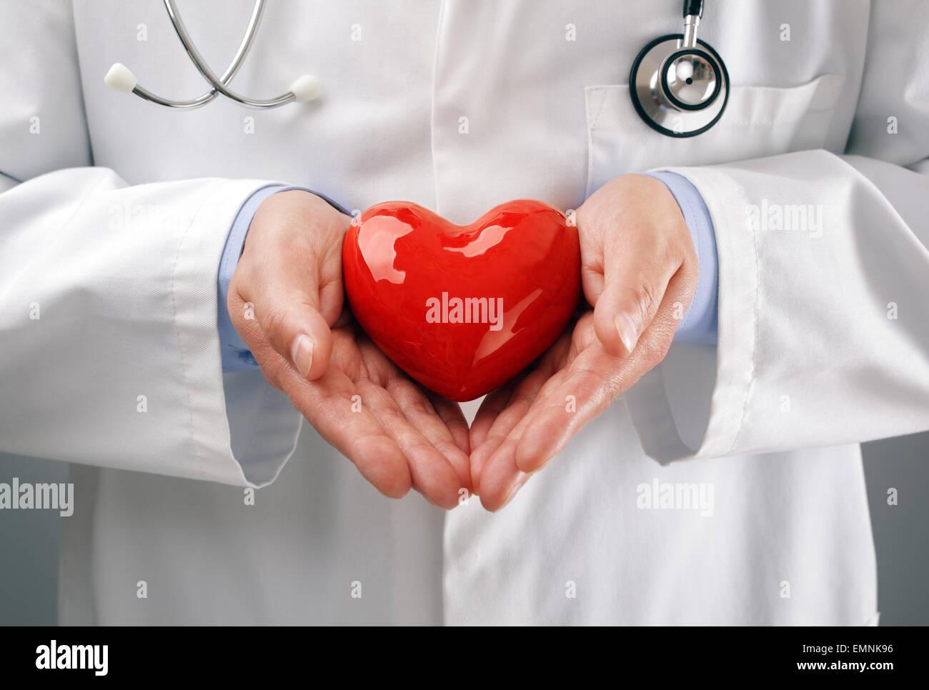 Arzt halten Herz mit Sorgfalt Stockbild