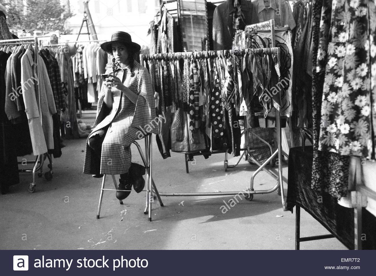 Eine Frau sitzt in Portobello Green Market, Vintage-Kleidung zu verkaufen. Notting Hill, London, England UK. Stockbild