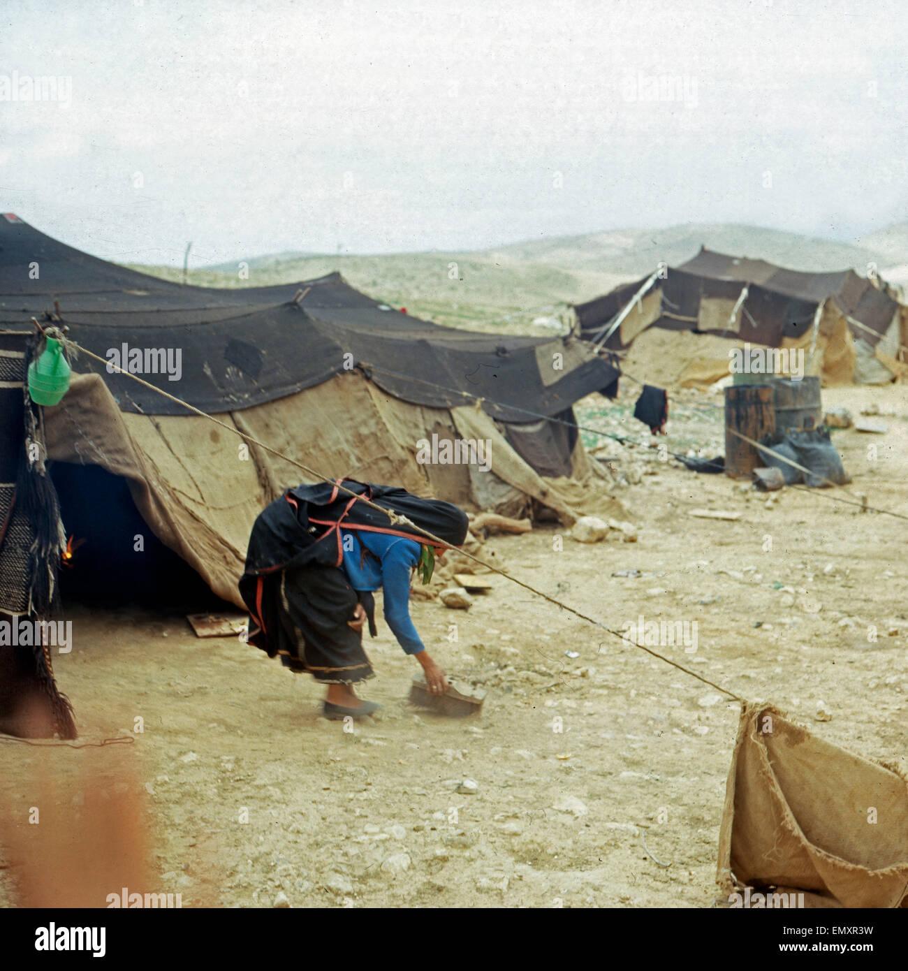 Eine Beduinenfrau Kehrt Vor Dachmarke Zelt Im Beduinenlager, Israel Ende 1970er Jahre. Eine Frau vor ihrem Zelt Stockbild