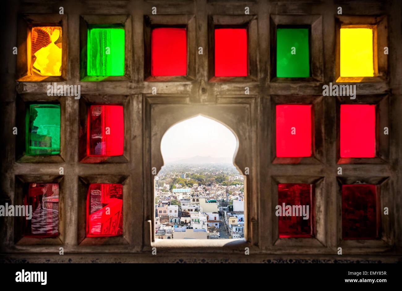 Blick auf die Stadt aus dem bunten Mosaik-Fenster im City Palace Museum von Udaipur, Rajasthan, Indien Stockbild