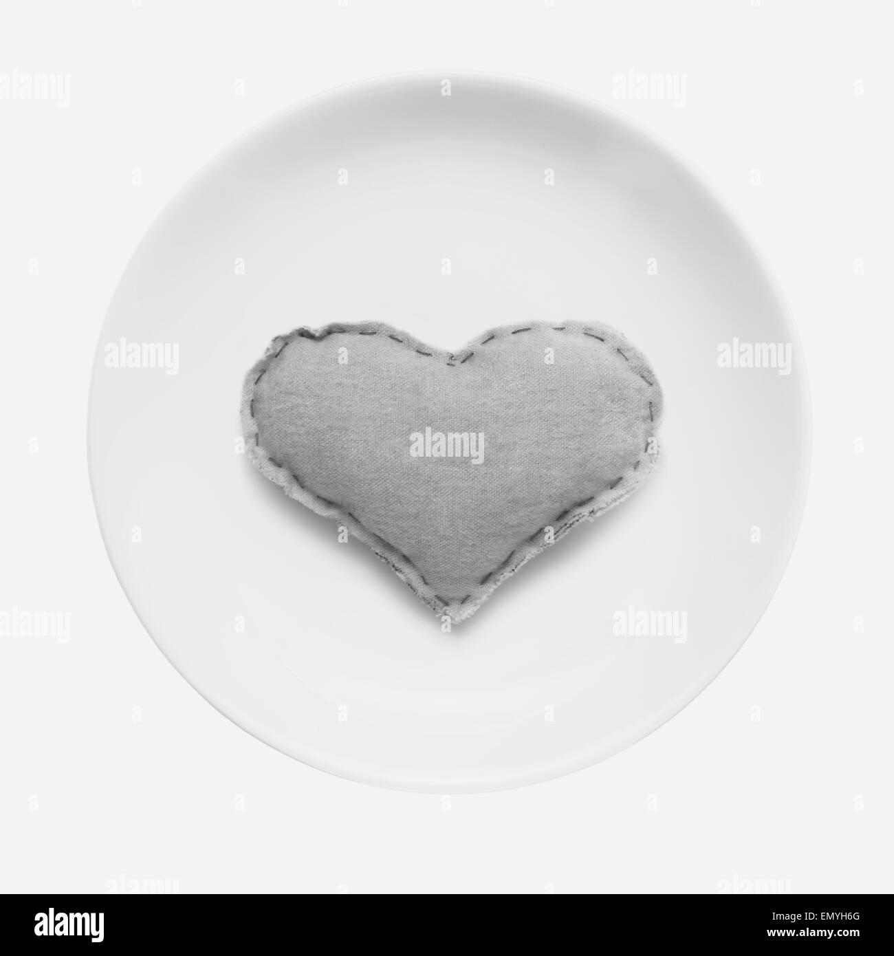 Weißen Teller mit handgefertigten Herz drauf. Schwarz / weiß minimalis Stockbild