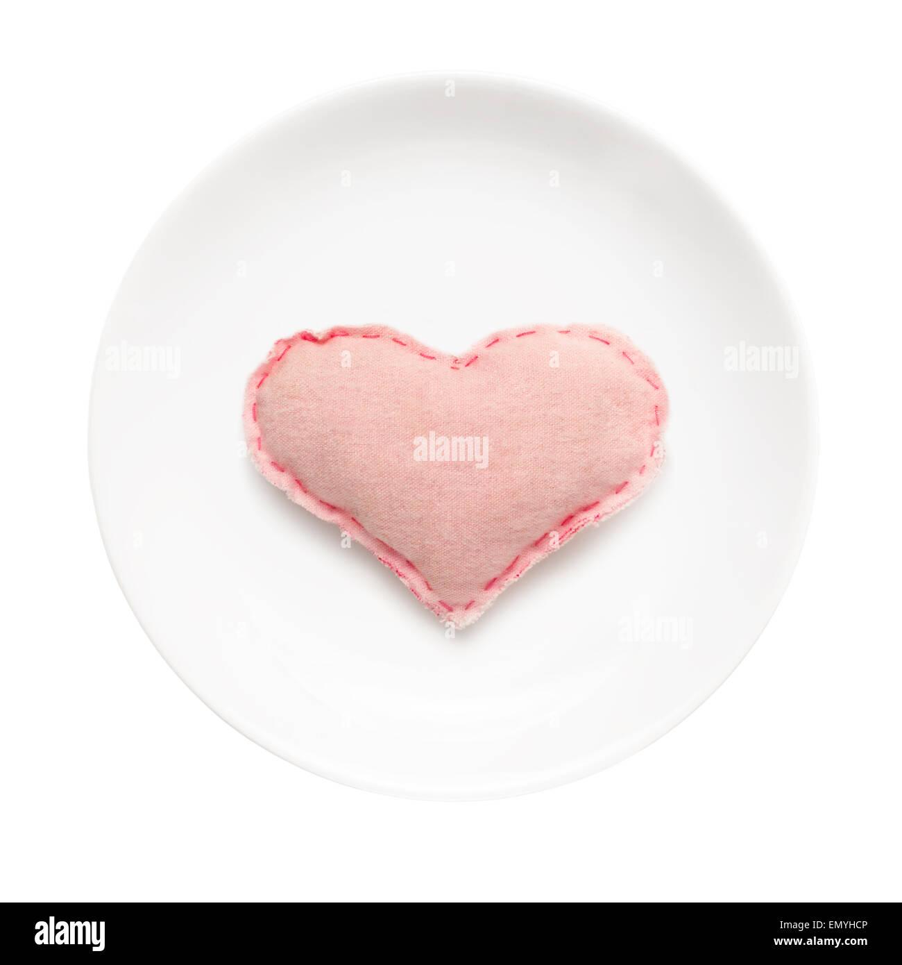 Weißen Teller mit handgefertigten Herz darauf isoliert auf weißem staatlich Stockbild
