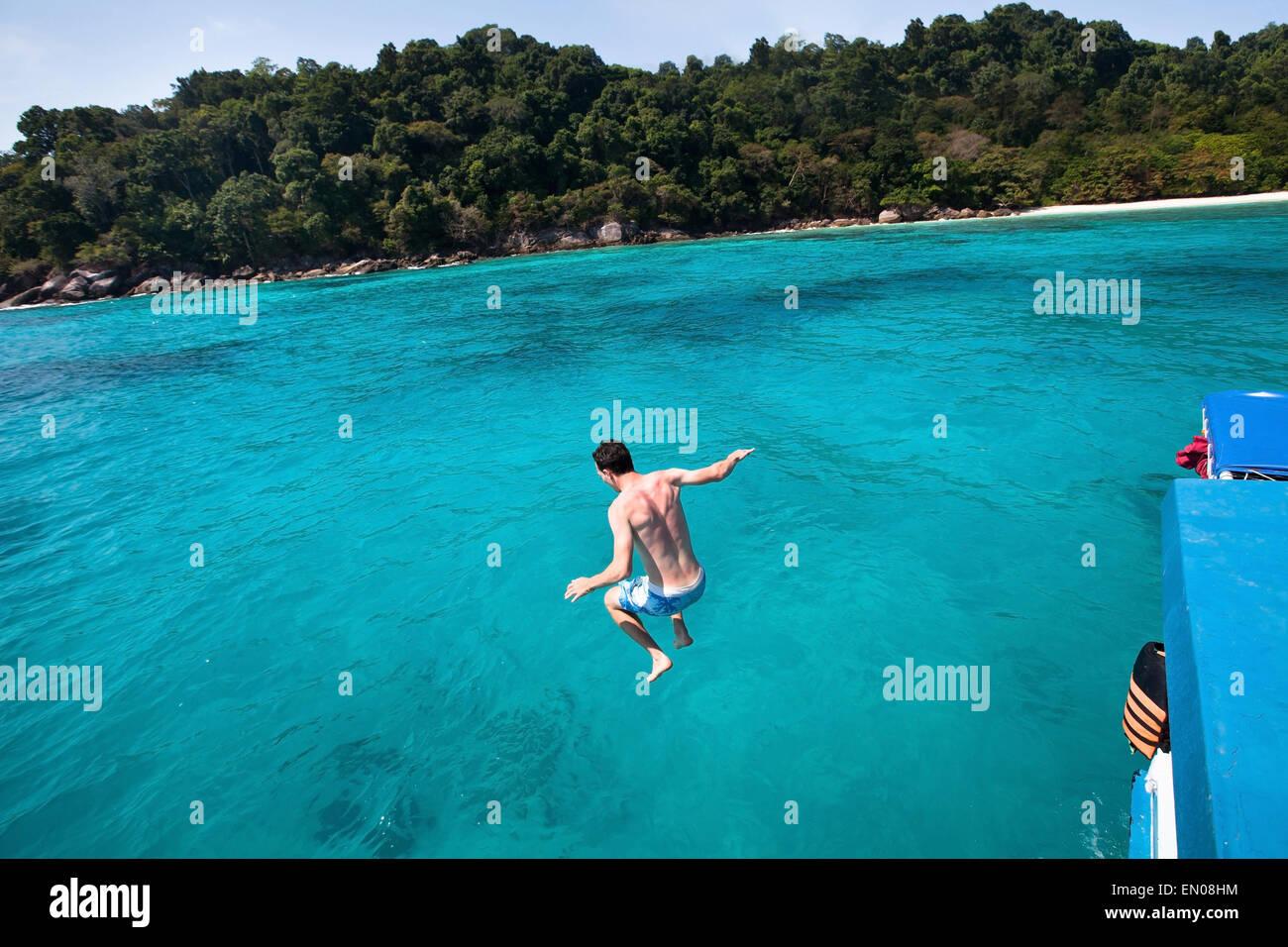 junger Mann springt auf das Meer von Yacht nahe dem Strand von Paradise island Stockbild