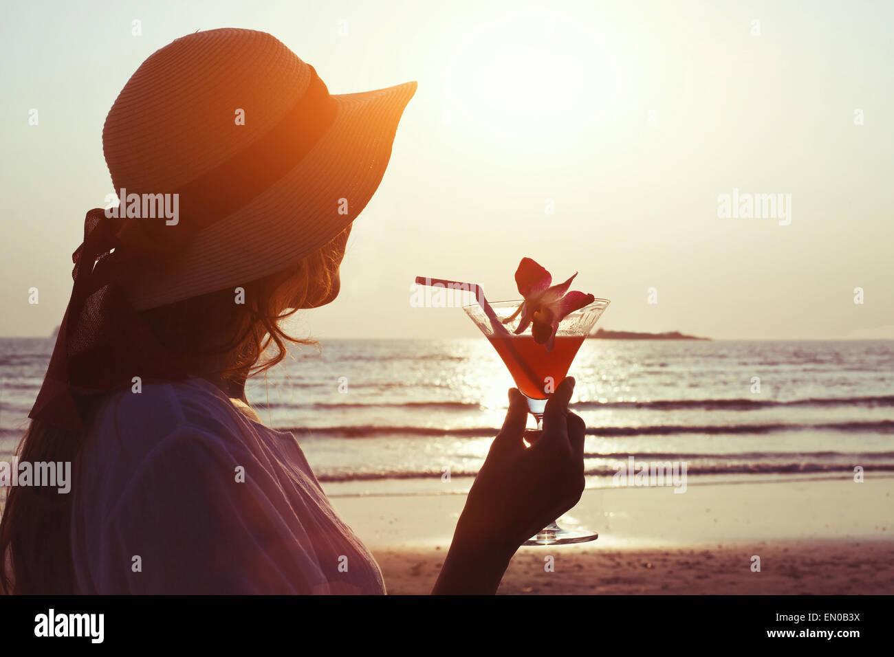Frau mit Cocktail bei Sonnenuntergang Strand Stockbild