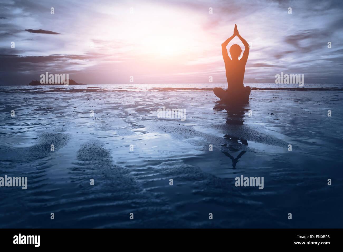 Wellness Konzept, wunderschönen Sonnenuntergang am Strand, Frau, Yoga zu praktizieren Stockbild