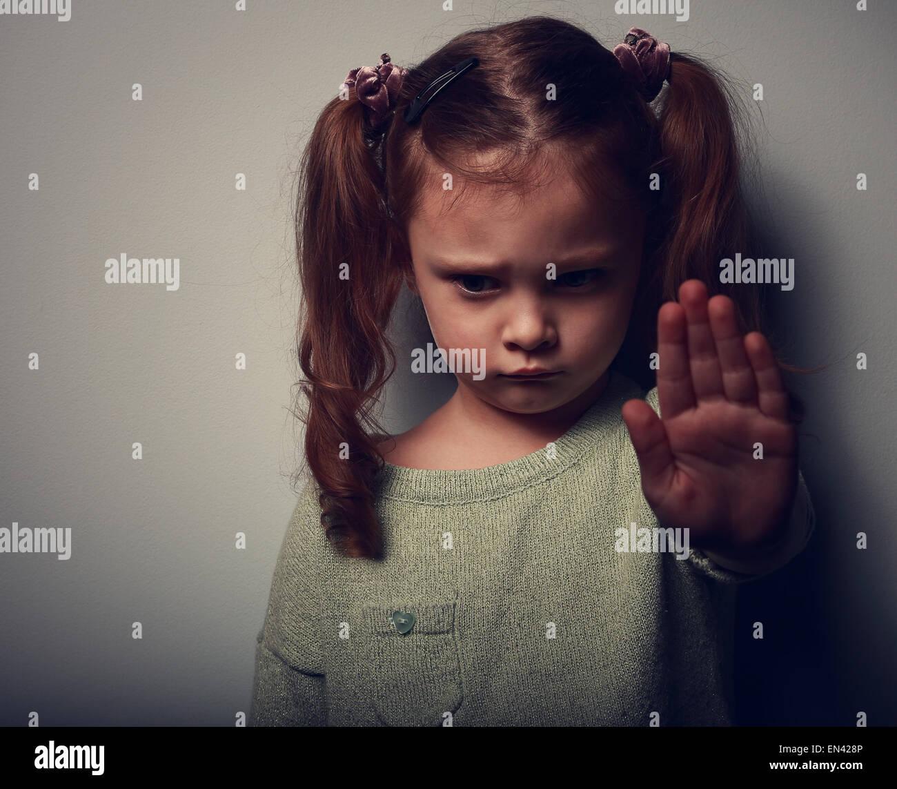 Kind Mädchen zeigen Hand-Signalisierung, Gewalt und Schmerz und blickte auf dunklem Hintergrund zu stoppen. Stockbild