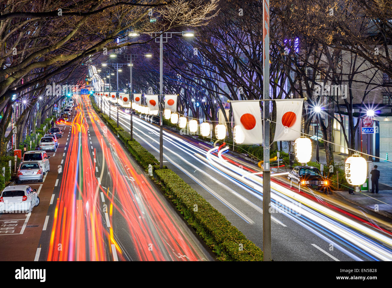 Harajuku, Tokyo, Japan Verkehrsströme unter japanischen Fahnen in der Nacht. Stockbild