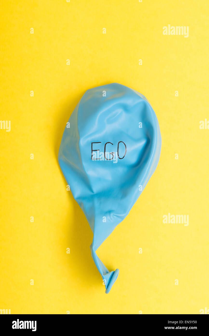 Blaue Luftballon auf gelbem Hintergrund mit dem Wort Ego drauf Stockbild