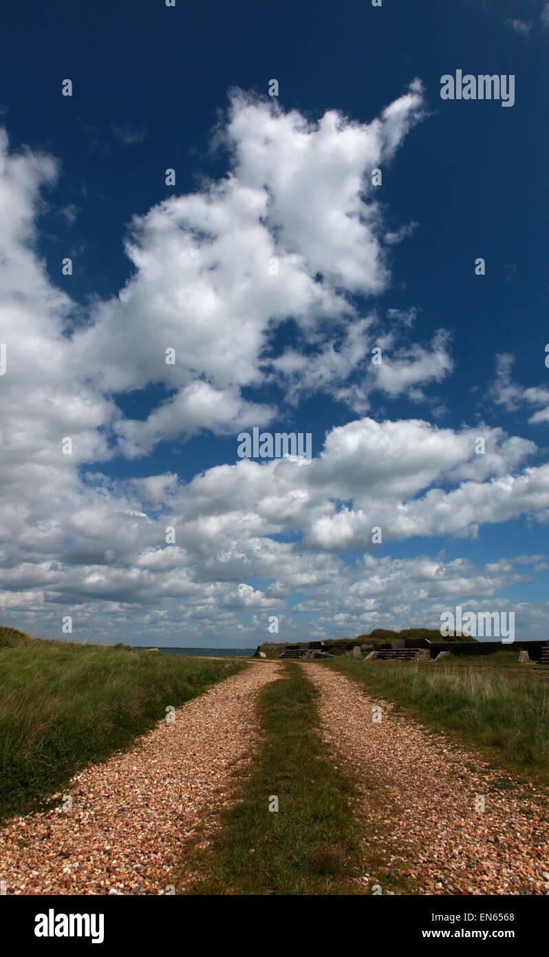Ein Kiesweg führt in die Ferne mit Wolken vor blauem Himmel Stockbild