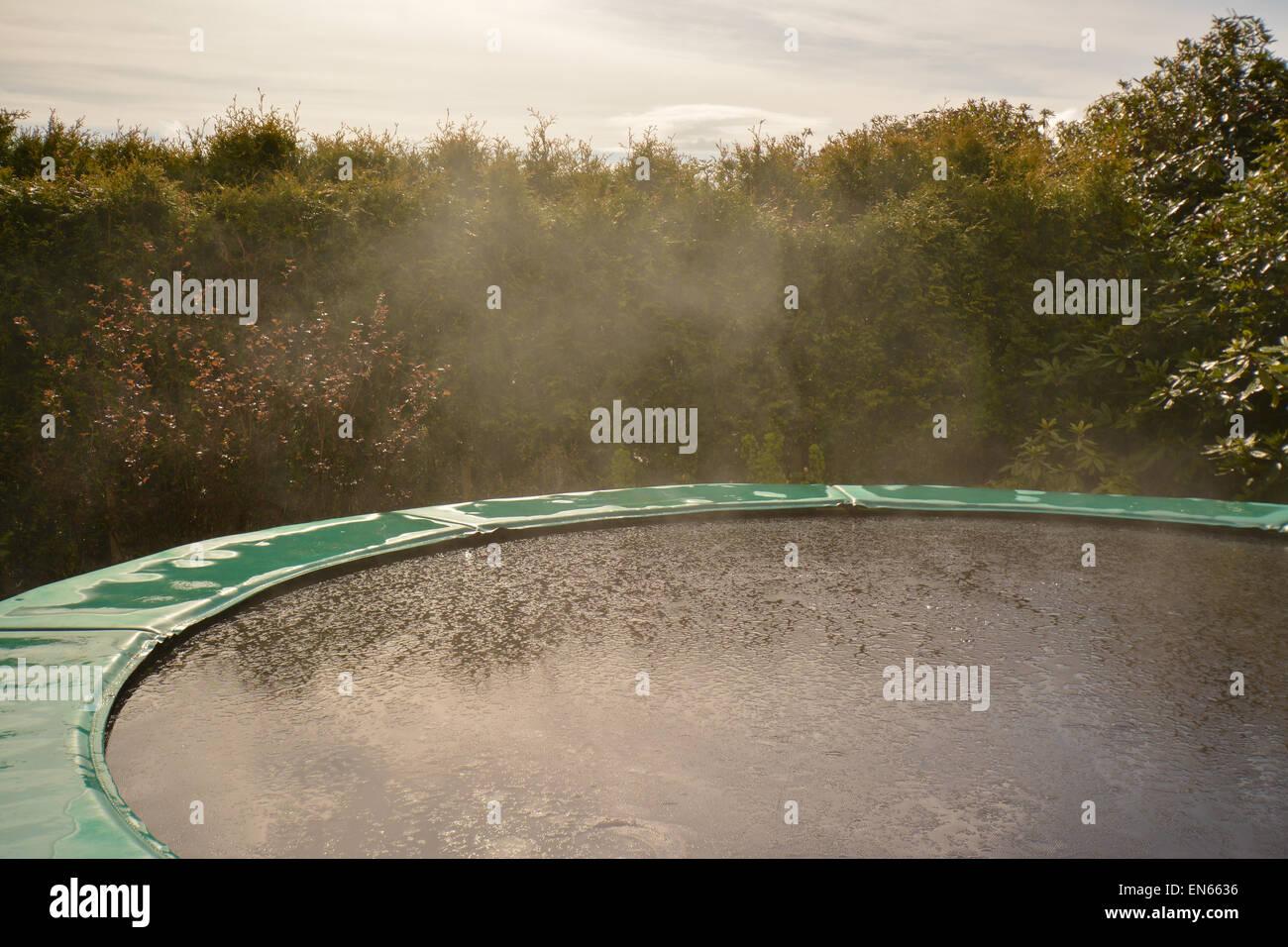 Beispiel für Verdampfung für Kinder - Verdampfen von Gartentrampolin nach plötzlichen Regen Regen Stockbild