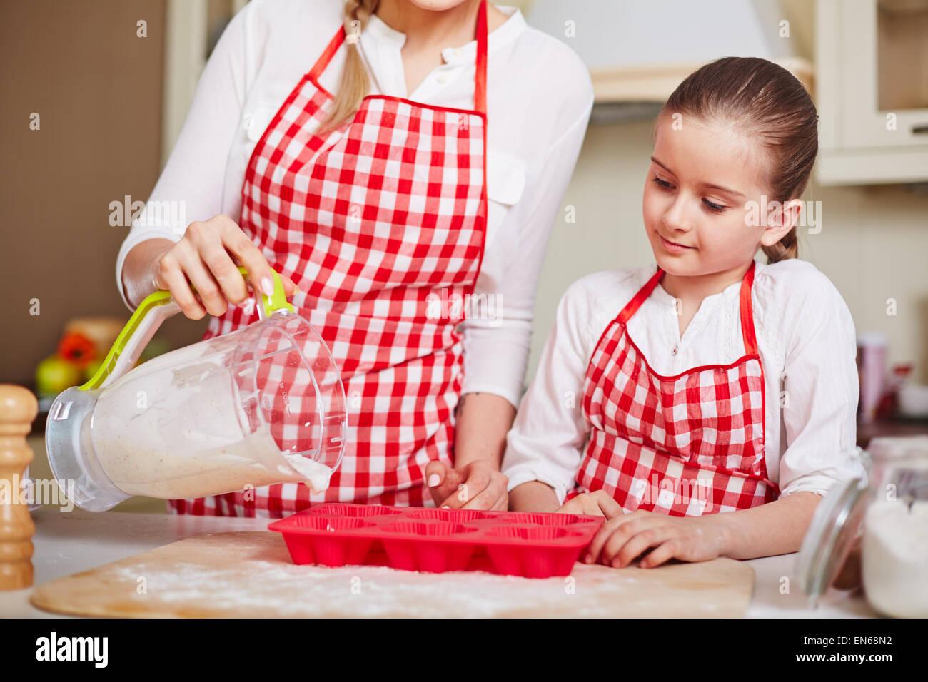 Neugierige Mädchen Blick auf ihre Mutter in Muffin-Formen mit flüssigen Teig füllen Stockbild