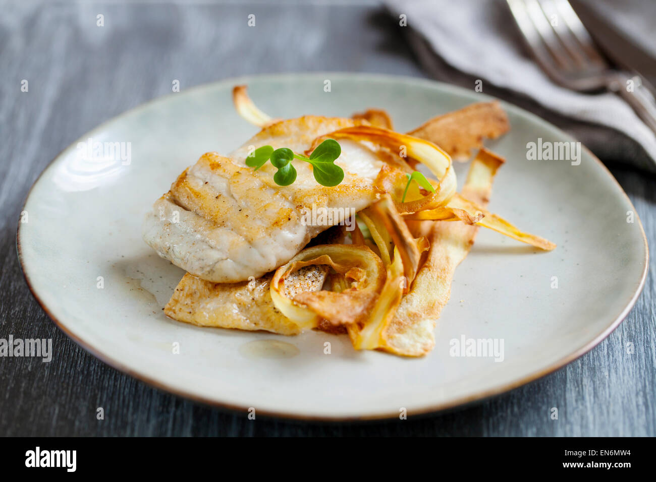 Pfanne gebratener Wolfsbarsch mit Pastinaken-Chips Stockbild