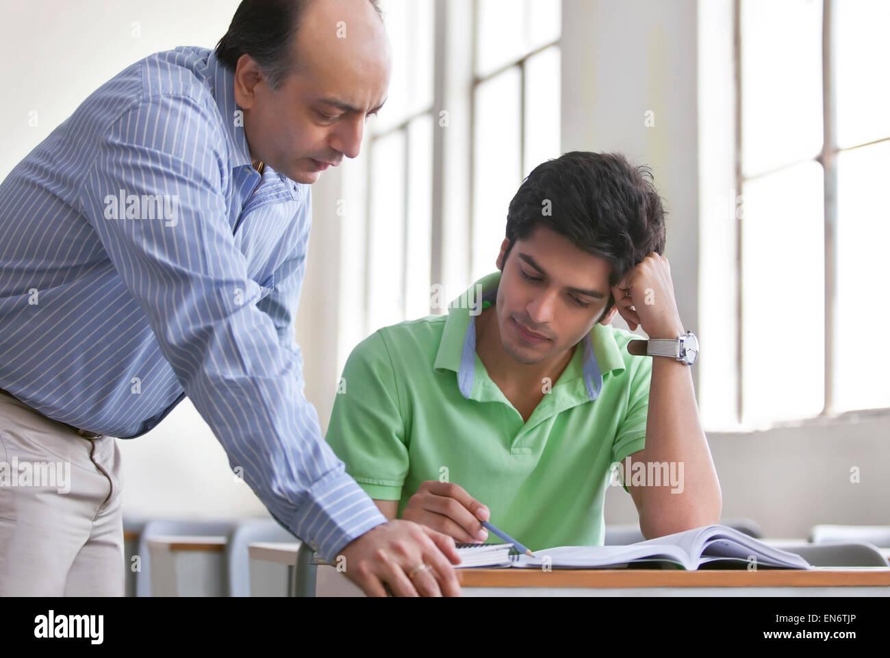 Lehrer helfen Schüler im Klassenzimmer Stockbild