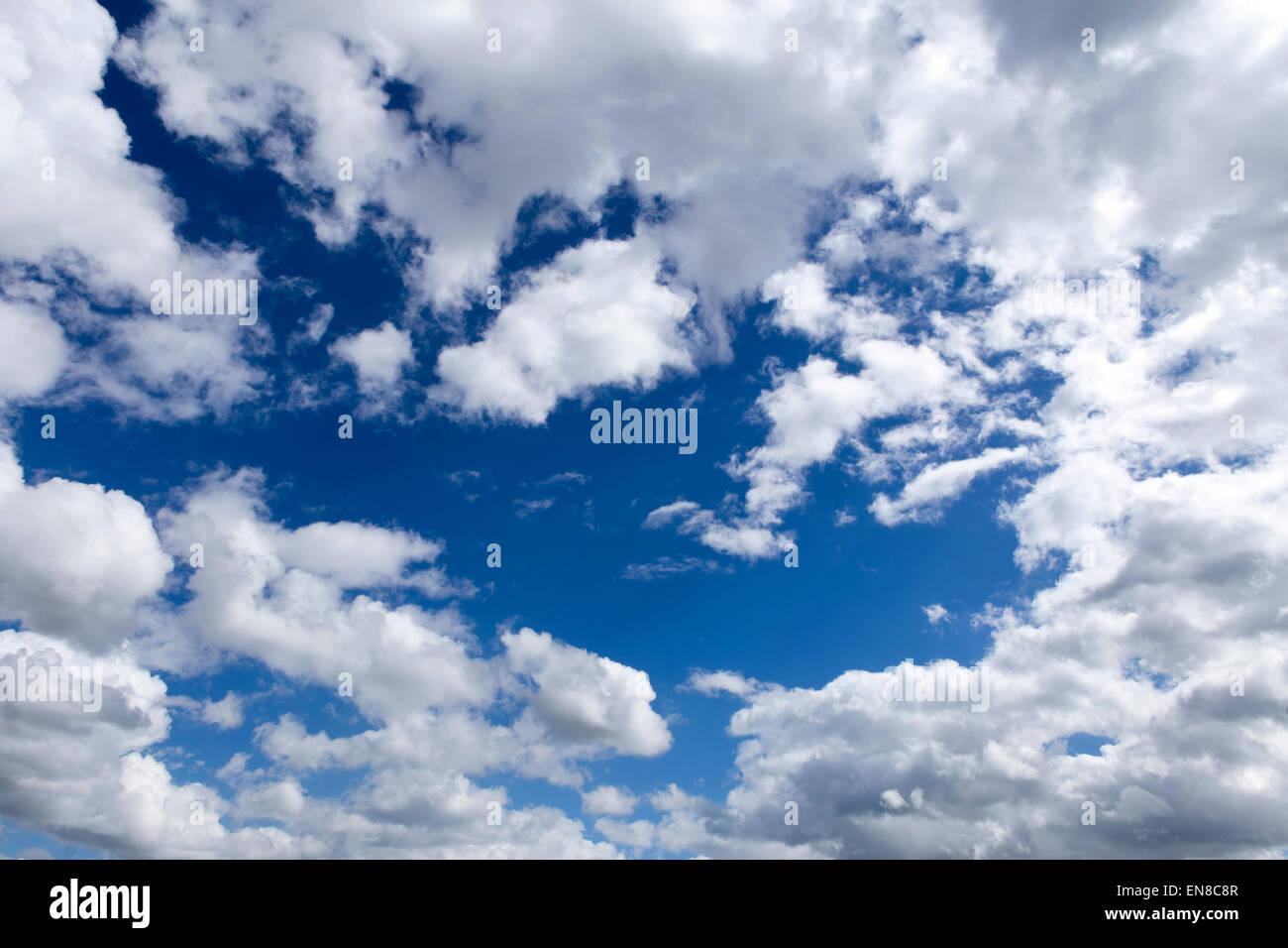 weiße Wolken in einem tiefblauen Himmel Stockbild