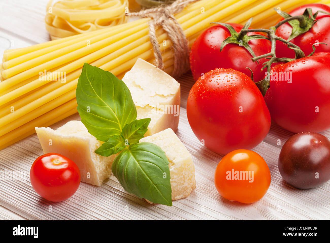 Italienische Küche kochen Zutaten. Nudeln, Tomaten, Basilikum auf Holztisch Stockbild