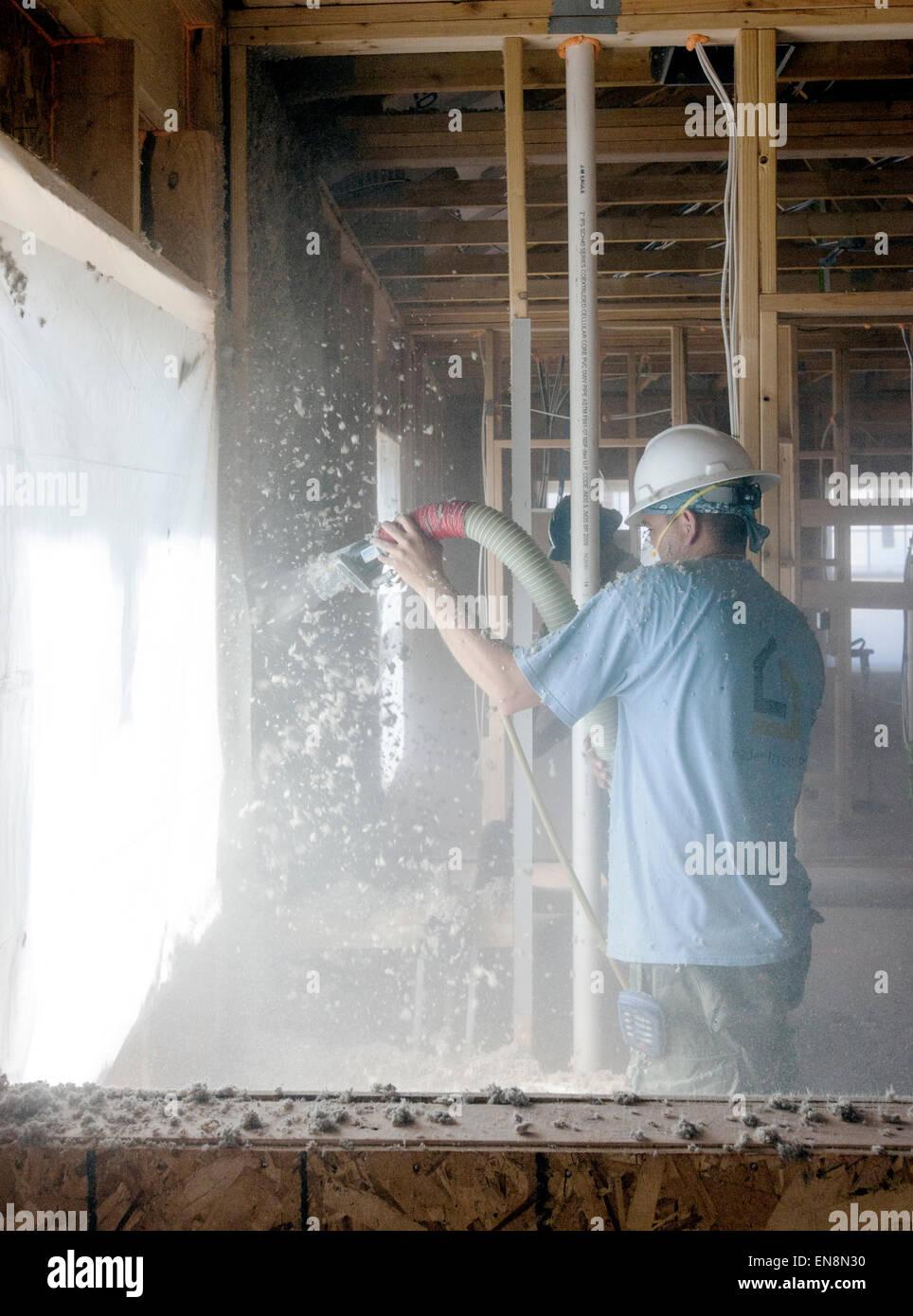 Arbeitnehmer, die Spritzen Zellulosedämmung in die Wände eines neuen Hauses im Bau Stockbild