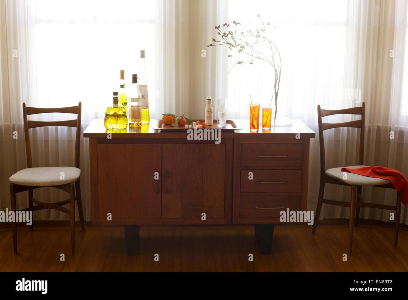 Eine Hausbar vor einem Fenster mit einem Flaschen Schnaps, Orangen ...