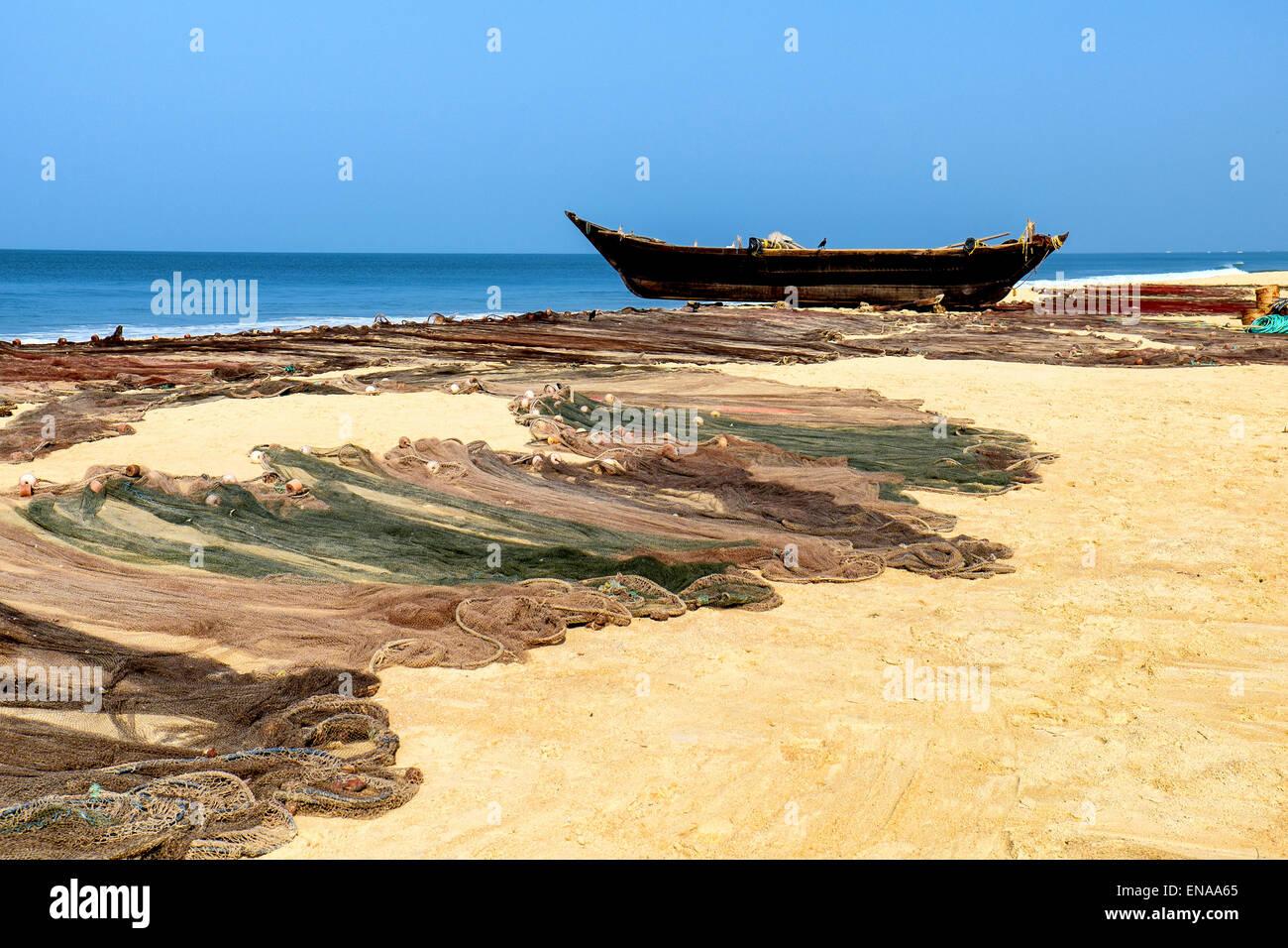 Goan Fischerboot mit Fischernetzen im Vordergrund in Cavelossim, Salcette Goa Stockbild