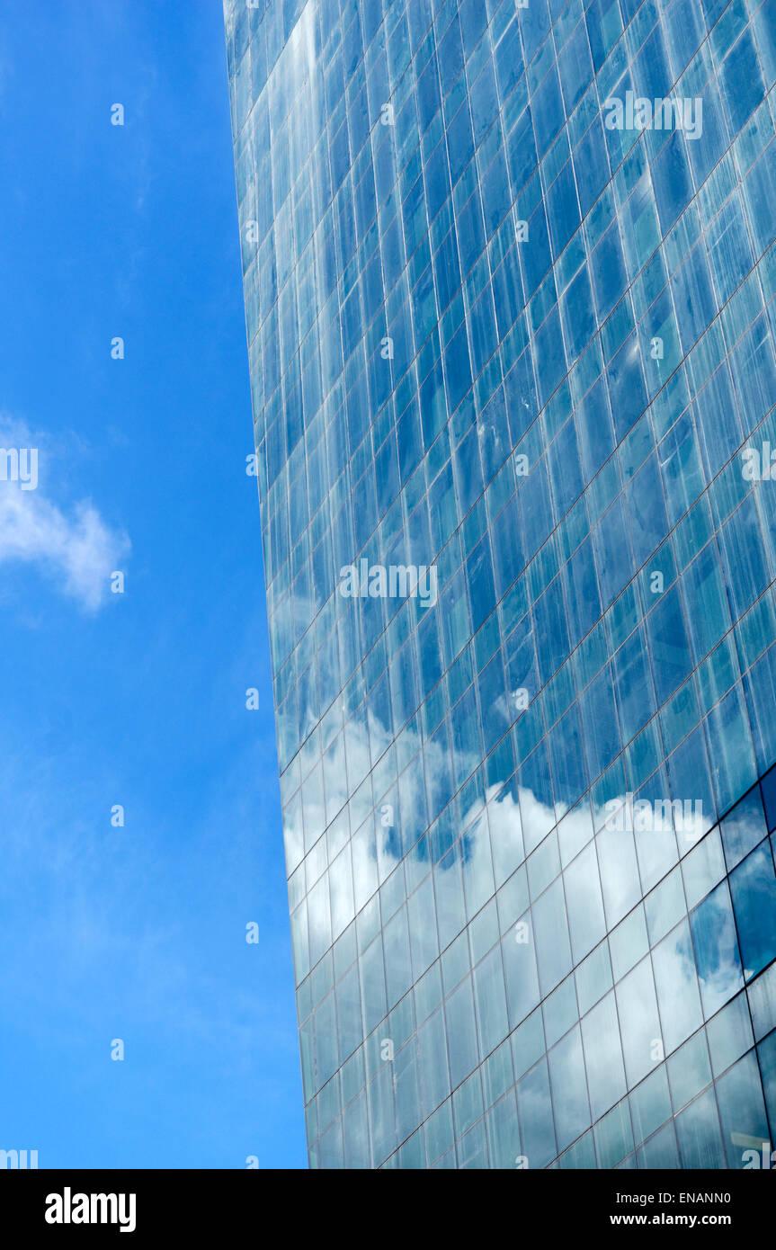 Wolken und blauer Himmel spiegelt sich in der Glasfassade ein Büroturm in der Innenstadt von Vancouver, BC, Stockbild