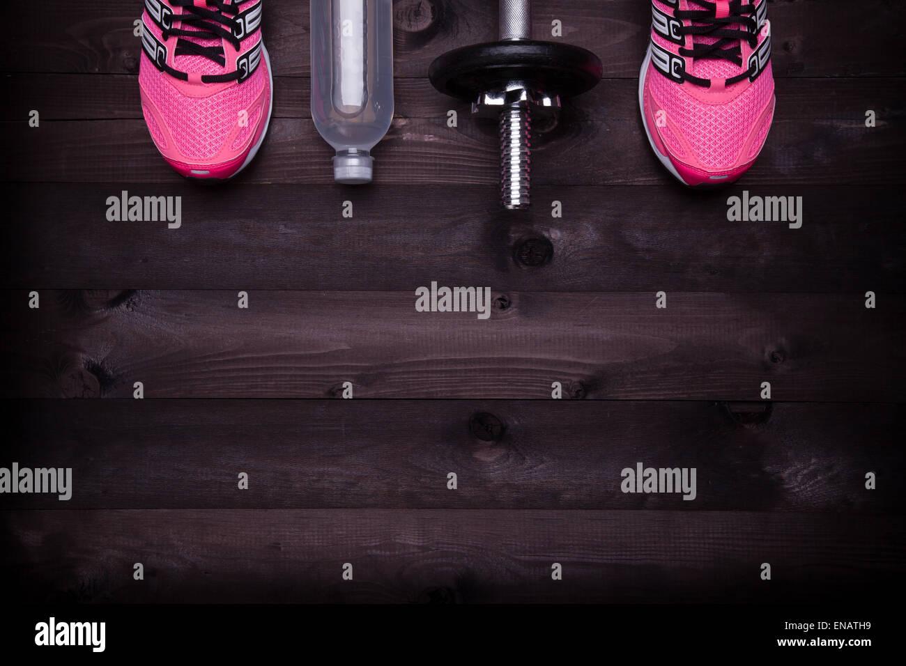 Sportgeräte. Turnschuhe, Wasser und eine Hantel auf einem schwarzen Hintergrund aus Holz Stockbild