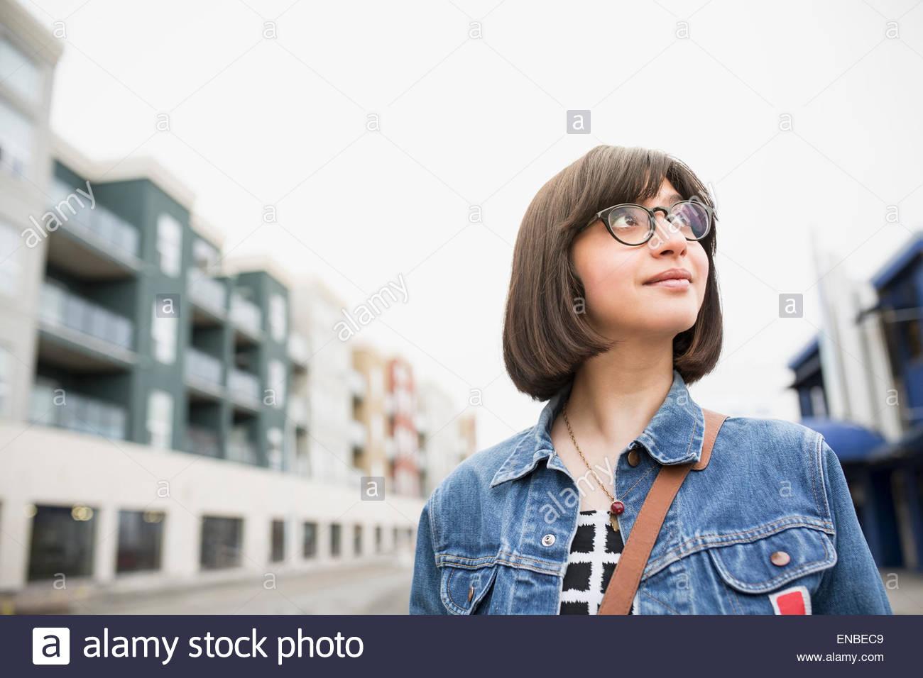 Frau in Jeansjacke auf städtischen Straße Stockbild